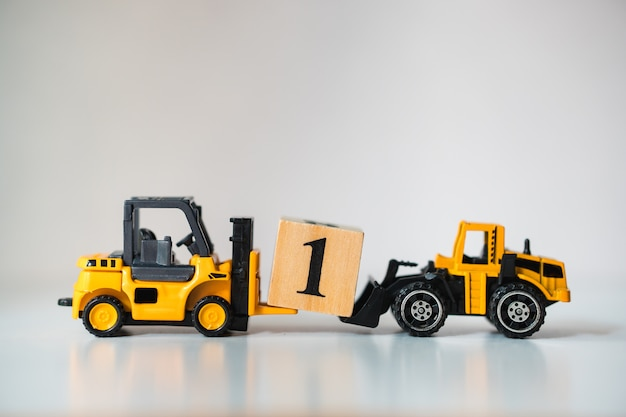 Chariot élévateur miniature soulevant un bloc de bois numéro un