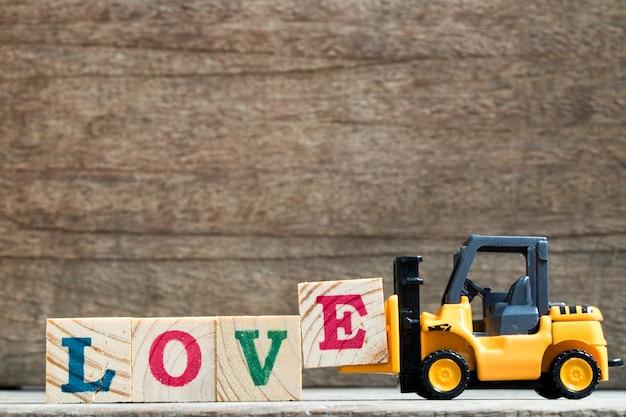 Le chariot élévateur en plastique de jouet tiennent le bloc e pour composer et accomplir l'amour de formulation sur le fond en bois