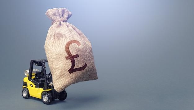 Chariot élévateur transportant un sac d'argent en livre sterling. aide financière la plus forte
