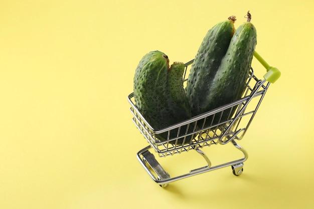 Chariot d'épicerie avec deux concombres laids sur table jaune vif. concept shopping environnemental, alimentation biologique