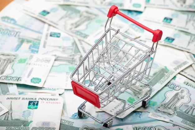 Chariot d'épicerie avec une poignée rouge sur fond de billets de 1000 roubles.