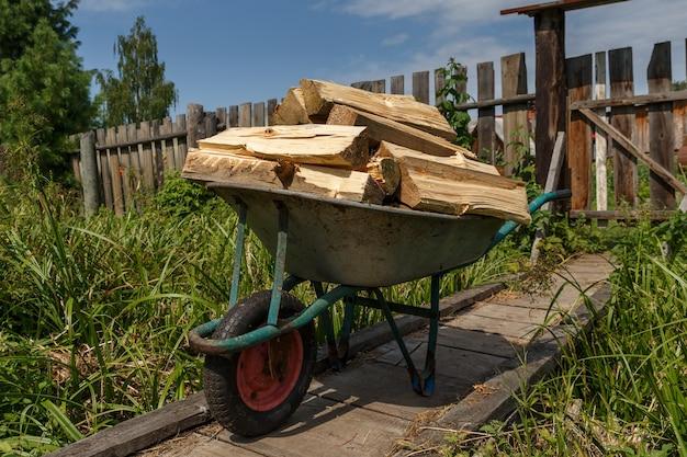 Un chariot de jardin avec du bois haché se dresse sur un pont en bois.