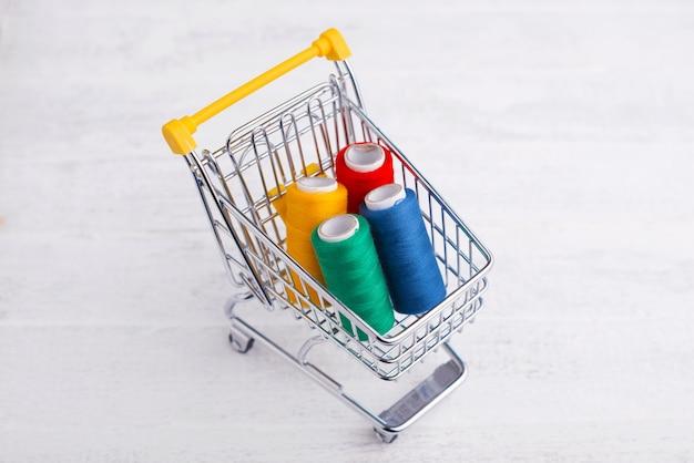 Chariot jaune avec fil coloré, concept de magasinage en ligne