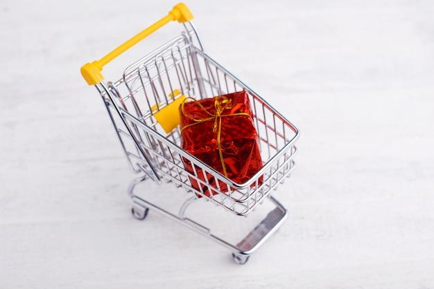Chariot jaune avec grande boîte cadeau rouge pour noël ou anniversaire, concept de magasinage en ligne