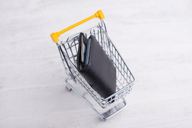 Chariot jaune avec portefeuille noir, concept de magasinage en ligne