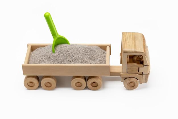 Un chariot de jouets en bois miniature rempli de sable avec une pelle verte dedans amusant pour les garçons libre de pentecôte