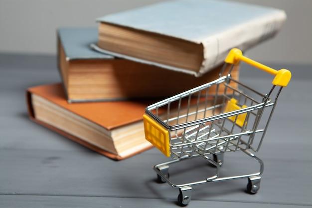 Chariot et livres sur la table. concept d'achat de livres sur fond gris
