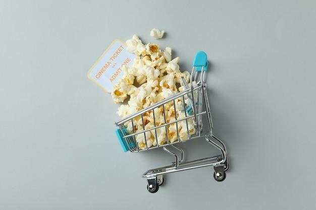 Chariot de magasin avec pop-corn et ticket sur fond gris clair.