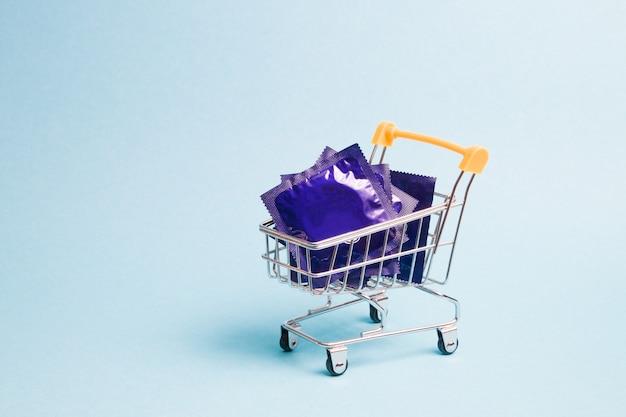 Chariot de magasinage d'emballage de préservatif sur fond bleu espace copie concept safe sex