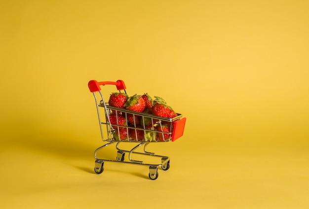 Chariot en métal avec des fraises sur une pièce isolée jaune