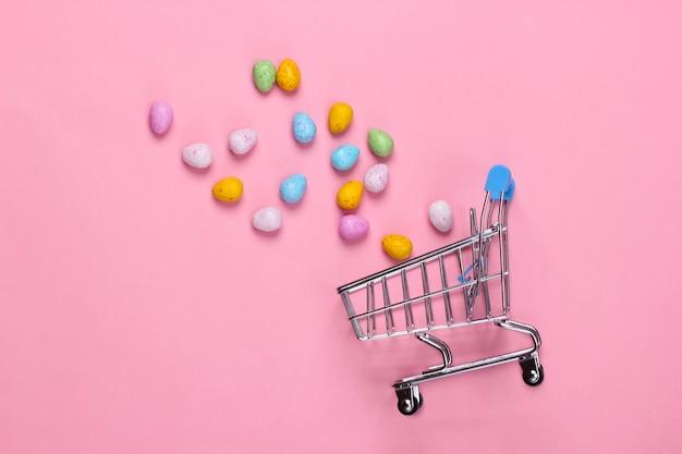 Chariot de mini supermarché avec mini oeufs de pâques sur un rose pastel. minimalisme de pâques