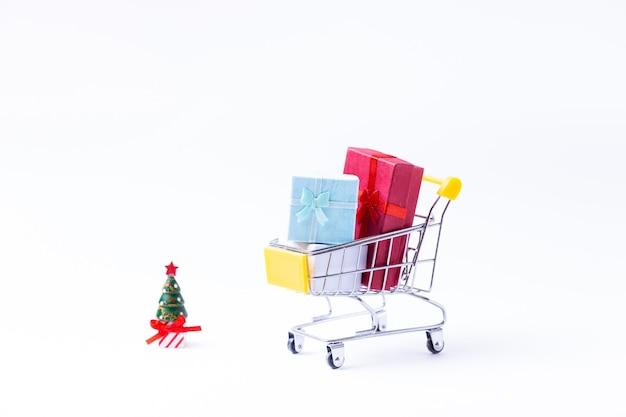 Chariot Miniature Avec Des Cadeaux Sur Une Surface Blanche. Concept De Magasinage De Noël Et Du Nouvel An. Fermer. Photo Premium