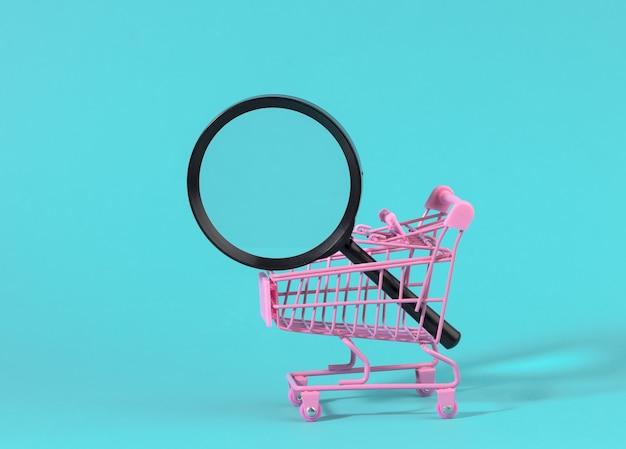 Chariot miniature en métal rose et loupe en plastique noir sur une surface bleu clair. le concept de recherche et de sélection d'achats, d'économies