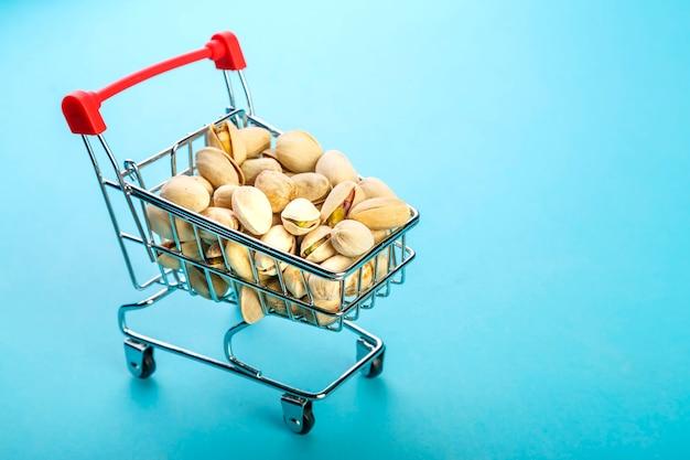 Chariot de nourriture rempli de pistaches dans des coquilles sur une surface bleue
