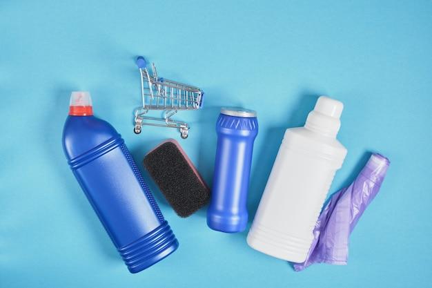Chariot à provisions et bouteille de détergent sans étiquettes sur l'ensemble de nettoyage de fond bleu. vue de dessus. concept de service de nettoyage