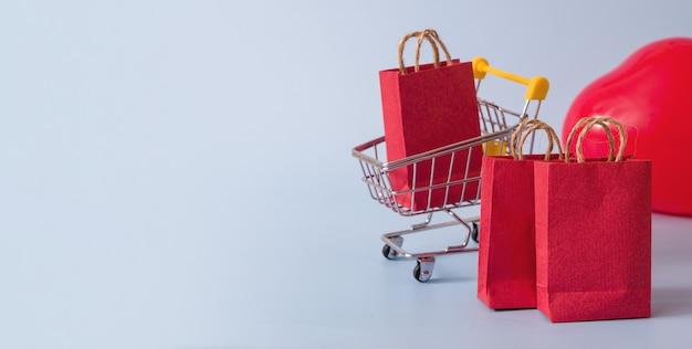 Chariot de supermarché avec des achats sur le fond de ballons en forme de coeur - bannière concept de la saint-valentin