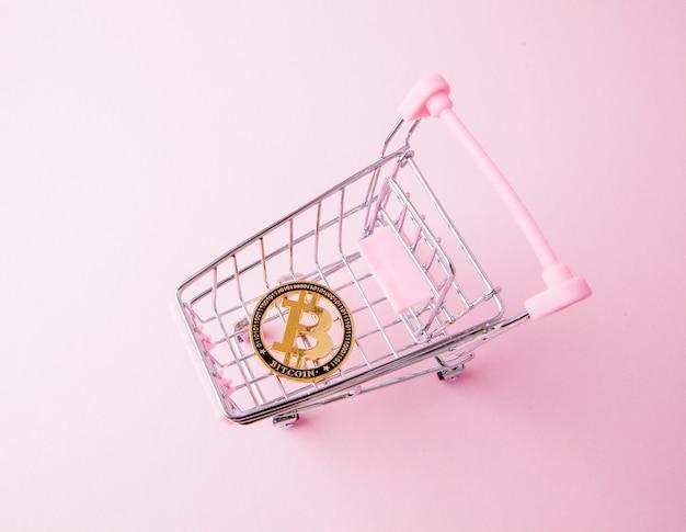 Un chariot d'un supermarché, bitcoin sur un bois. internet, crypto-monnaie.
