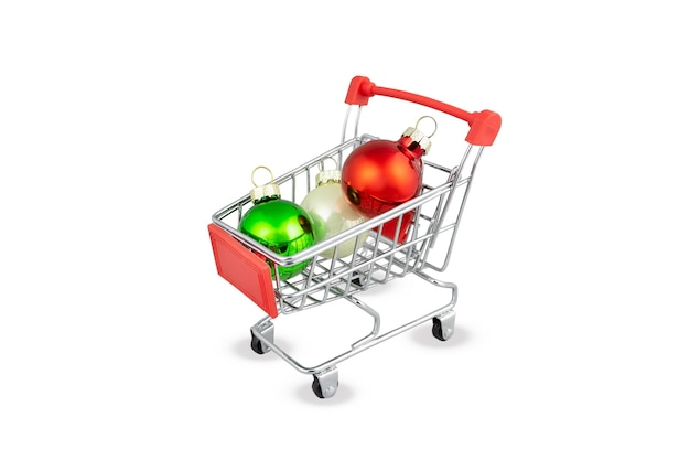 Chariot de supermarché avec boules de noël rouges, vertes et blanches. panier, symbole de vente pour le nouvel an ou noël. isolé sur une surface blanche.