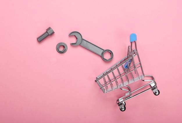 Chariot de supermarché avec clé jouet sur fond rose pastel. vue de dessus