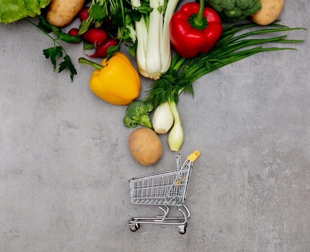 Chariot de supermarché et légumes sur une table