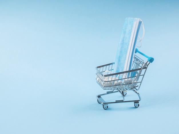 Chariot de supermarché avec des médicaments blancs et des masques