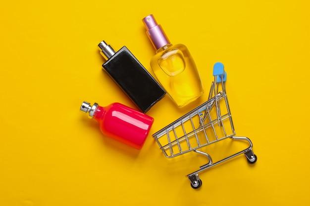 Chariot de supermarché mini avec des bouteilles de parfum sur un jaune, le minimalisme