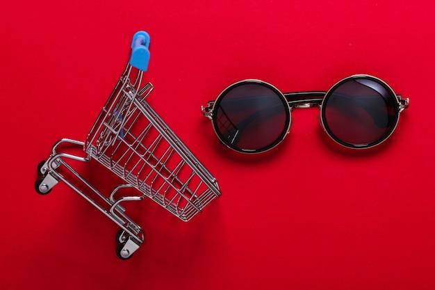 Chariot de supermarché mini avec des lunettes de soleil rondes sur rouge