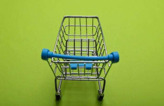 Chariot de supermarché mini sur vert. concept de magasinage