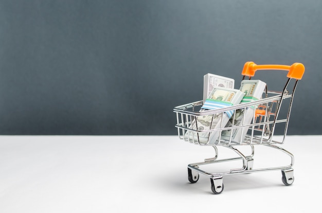 Chariot de supermarché avec des paquets de dollars