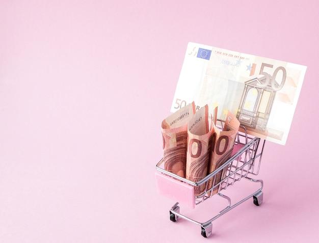 Chariot de supermarché plein de billets en euros sur rose