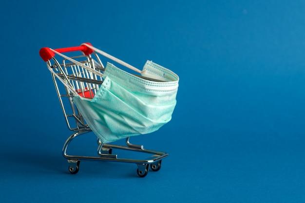 Chariot de supermarché pour faire du shopping avec masque