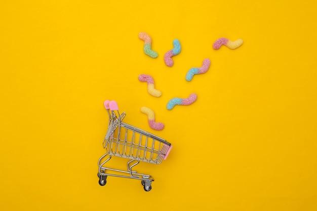 Chariot de supermarché avec vers gommeux sur fond jaune. vue de dessus