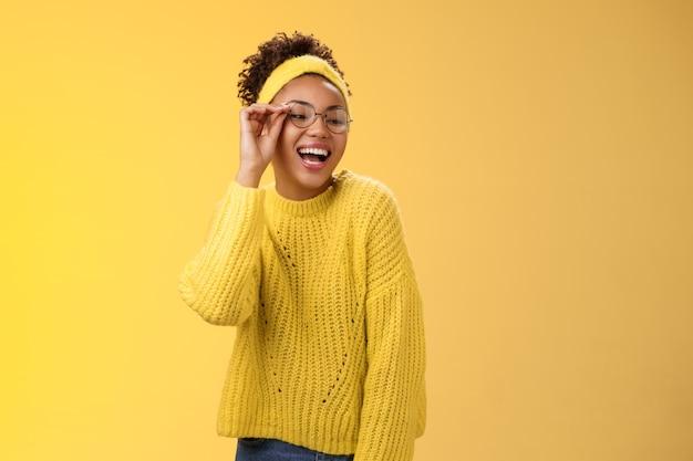 Charismatique élégante confiante belle adolescente joyeuse afro-américaine touchant le nez de lunettes en riant largement regarder vers le bas le coin droit souriant s'amuser en plaisantant en appréciant, fond jaune.