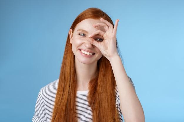 Charismatique heureux adorable rousse adolescente yeux sincères faisant cercle oeil montrer ok signe ok ravi comme approuver l'idée cool souriant satisfait atteindre le score parfait debout fond bleu