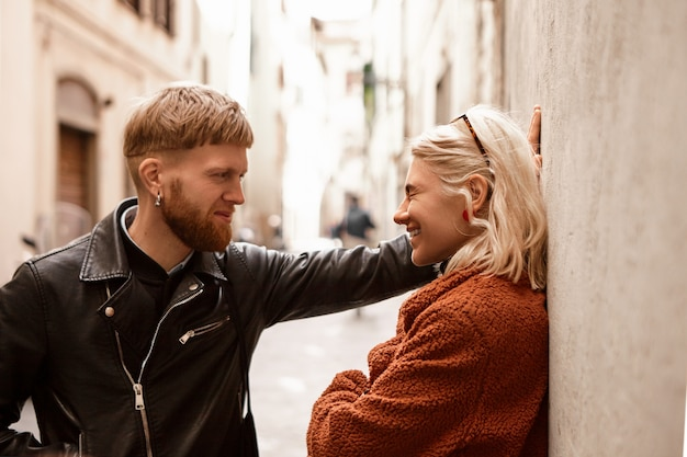 Charismatique jeune homme macho confiant avec une barbe épaisse au gingembre et une coupe de cheveux élégante conduisant une jolie femme étrangère blonde en riant au mur, lui demandant de sortir avec lui. concept d'amour, de convivialité et de romance