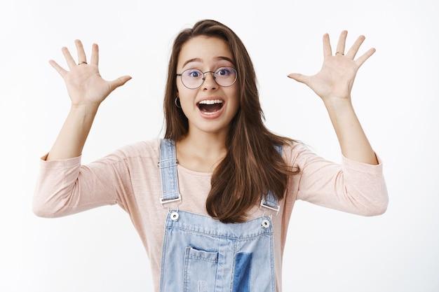 Charismatique surprise et excitée jeune femme mignonne heureuse dans des lunettes et des salopettes en jean agitant les mains levées avec étonnement criant oui de frisson et de bonheur, acclamant, célébrant la victoire.