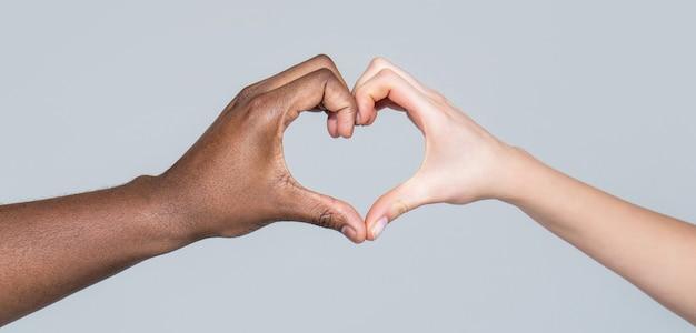 Charité, amour et diversité - gros plan sur des mains féminines et masculines de différentes couleurs de peau en forme de coeur. les gens de différentes couleurs de peau mettent leurs mains ensemble en forme de coeur sur fond blanc.