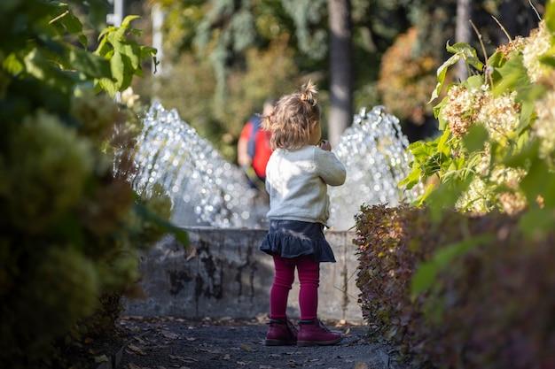 Charmant bambin dans le parc avec des fontaines en arrière-plan. jour d'été