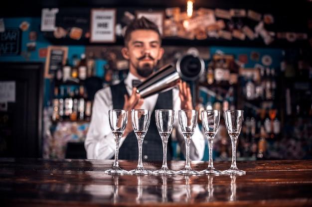 Un charmant barman ajoute des ingrédients à un cocktail dans la discothèque