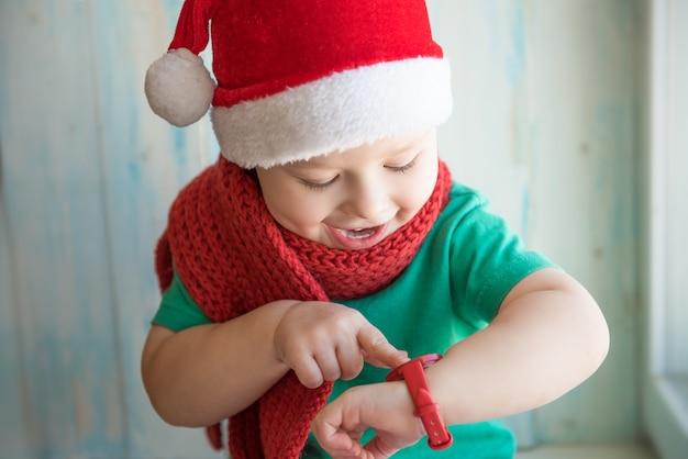 Charmant bébé dans un bonnet de noel pour voir l'heure