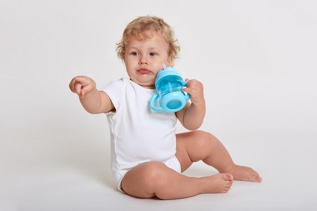 Charmant bébé veut boire de l'eau au biberon, en détournant les yeux, en pointant son index