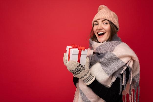 Charmant charmant heureux souriant jeune personne de sexe féminin brunet isolé sur mur de fond rouge
