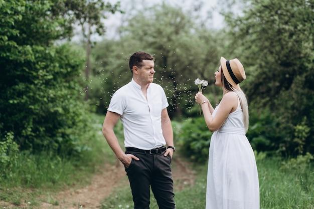 Le charmant couple amoureux debout sur l'herbe et soufflant des pissenlits