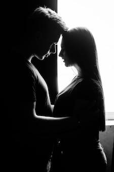Le charmant couple amoureux embrassant près de la fenêtre
