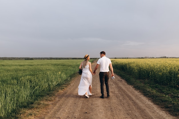 Le charmant couple amoureux marchant le long du champ