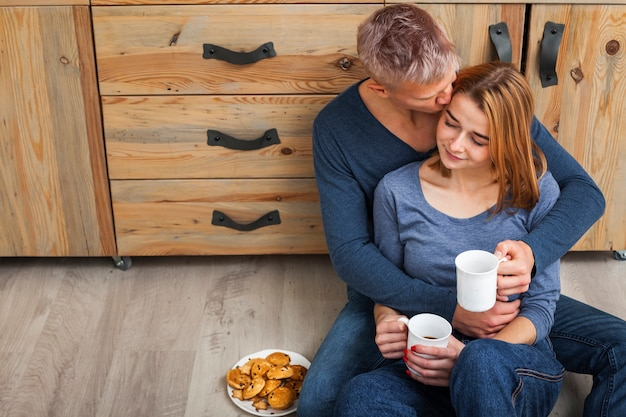 Charmant couple assis sur le sol de la cuisine