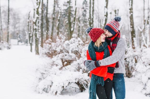 Charmant couple embrassant dans les bois enneigés