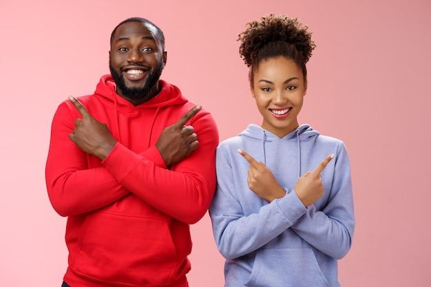 Charmant couple heureux petit ami afro-américain emménager ensemble en pointant différents côtés bras croisés poitrine gauche droite souriant largement optimiste ont une variété de bons choix opportunités