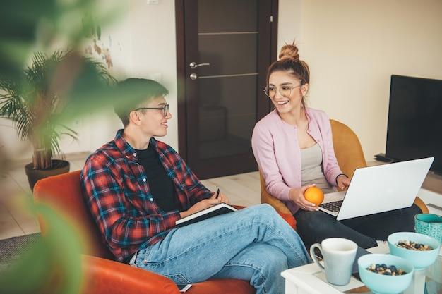 Charmant couple avec des lunettes assis dans un fauteuil et tenant un ordinateur portable tout en mangeant de l'orange et des céréales avec du lait