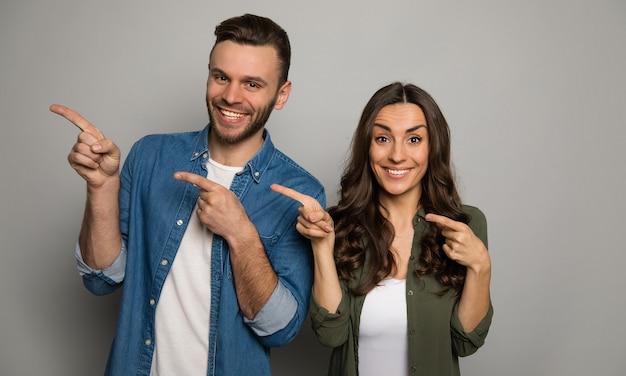 Un charmant couple pose sur un fond gris, portant des t-shirts blancs et des chemises colorées, pointant vers la gauche avec leurs mains et souriant à la caméra.